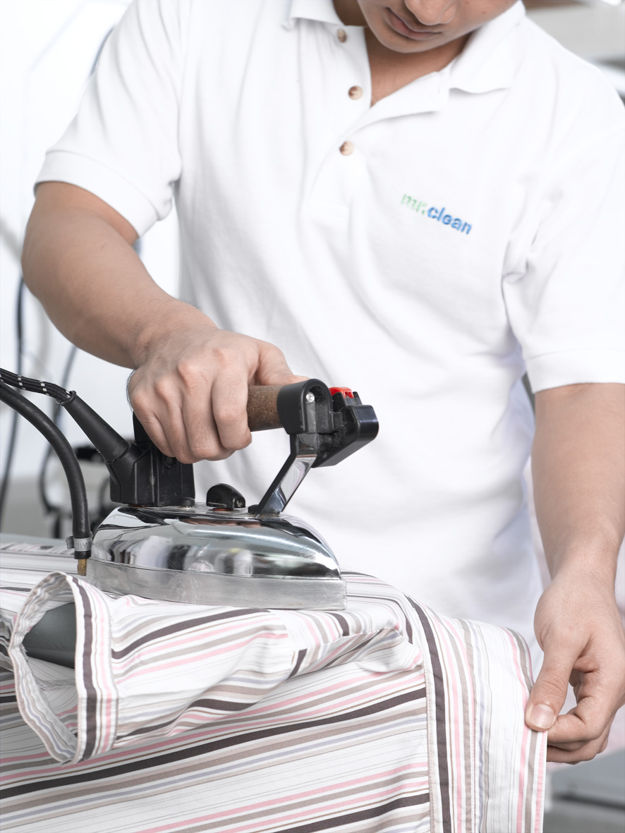 a mr clean staff is ironing the shirt
